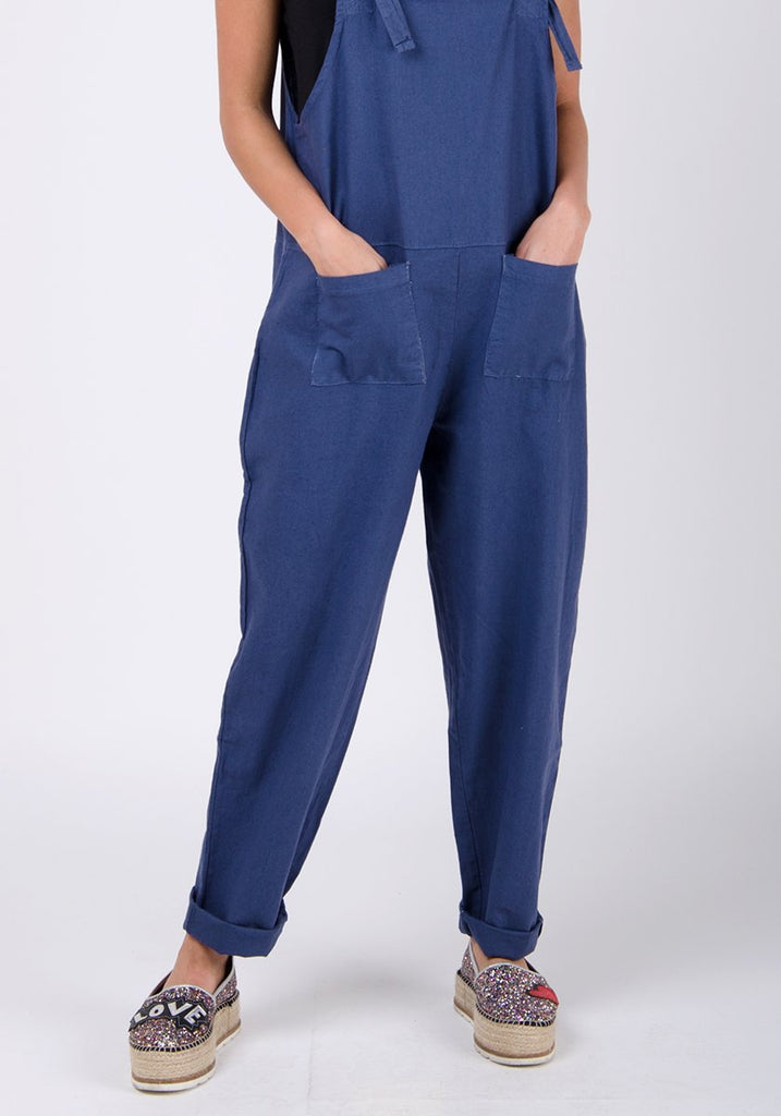 Lower two-thirds pose with hands in front pockets wearing basic linen, dungaree style jumpsuit.