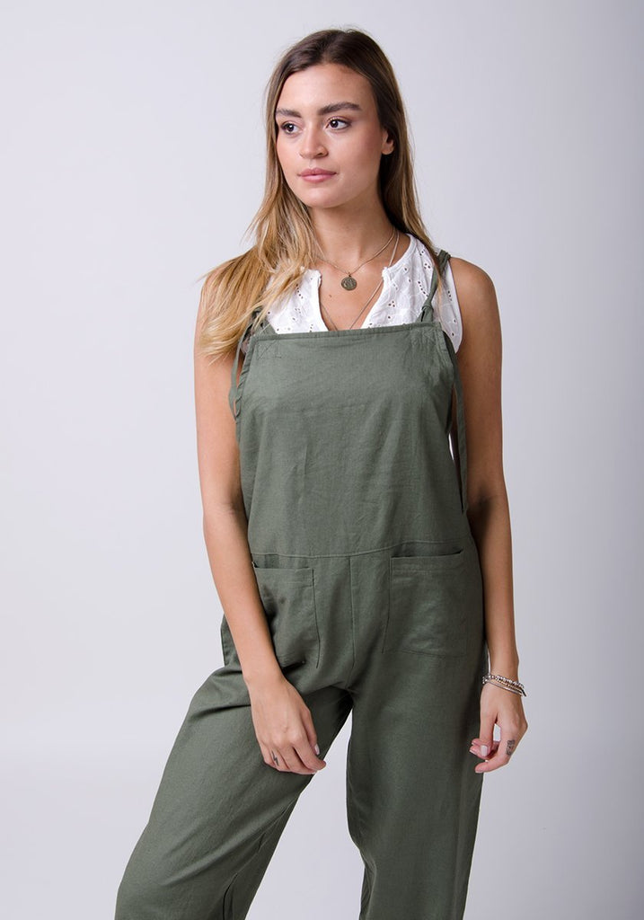 Two-thirds pose wearing basic linen, dungaree style jumpsuit.