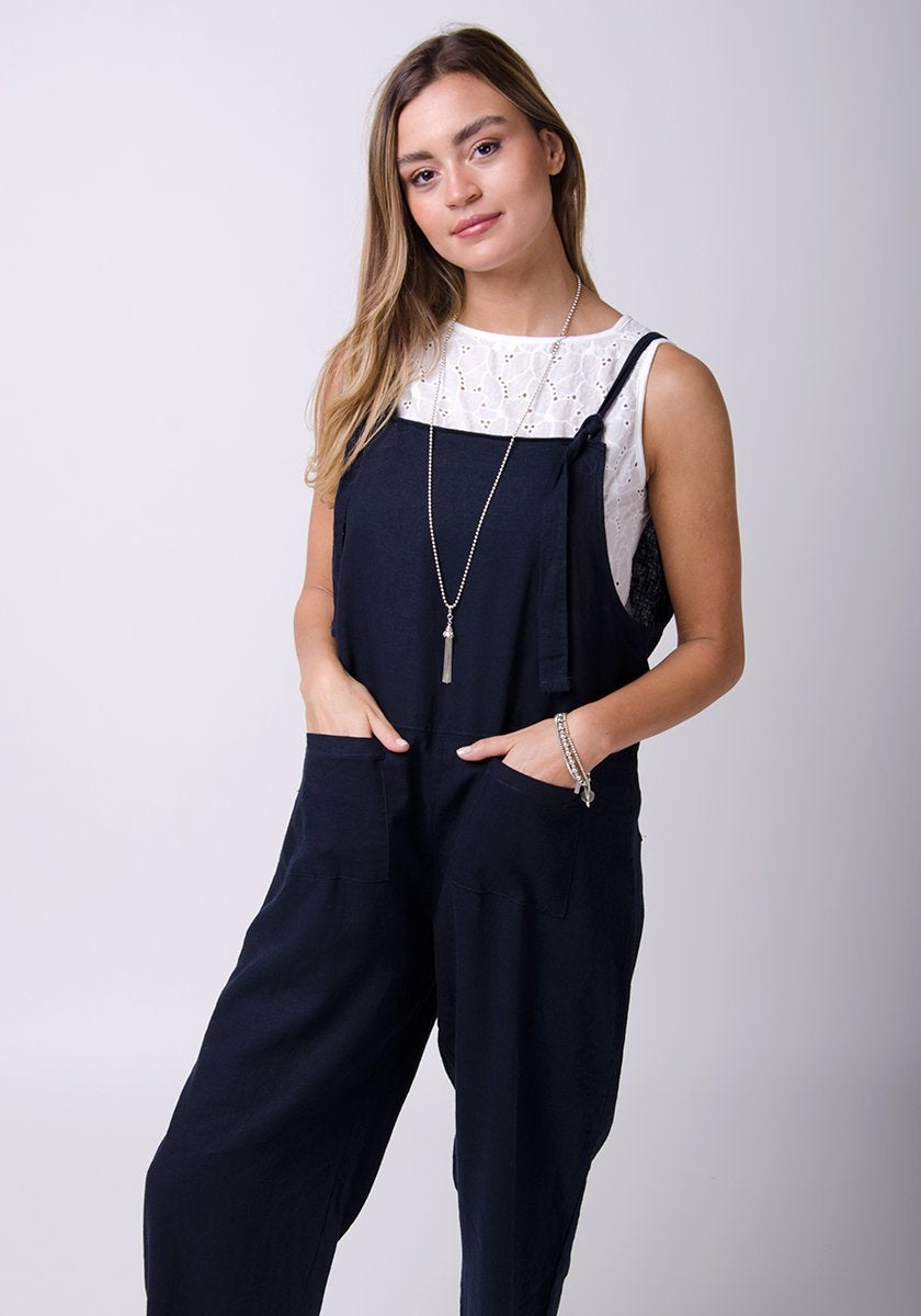 Two-thirds pose with hands in front pockets, wearing basic linen, dungaree style jumpsuit.