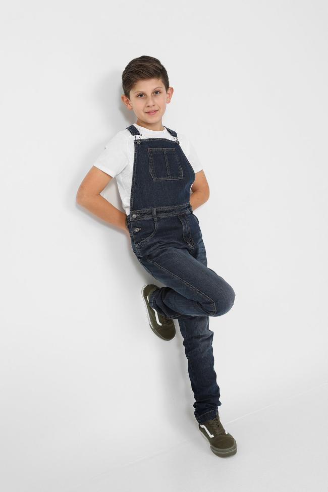 Full length pose leaning against wall wearing boys kids bib-overalls.