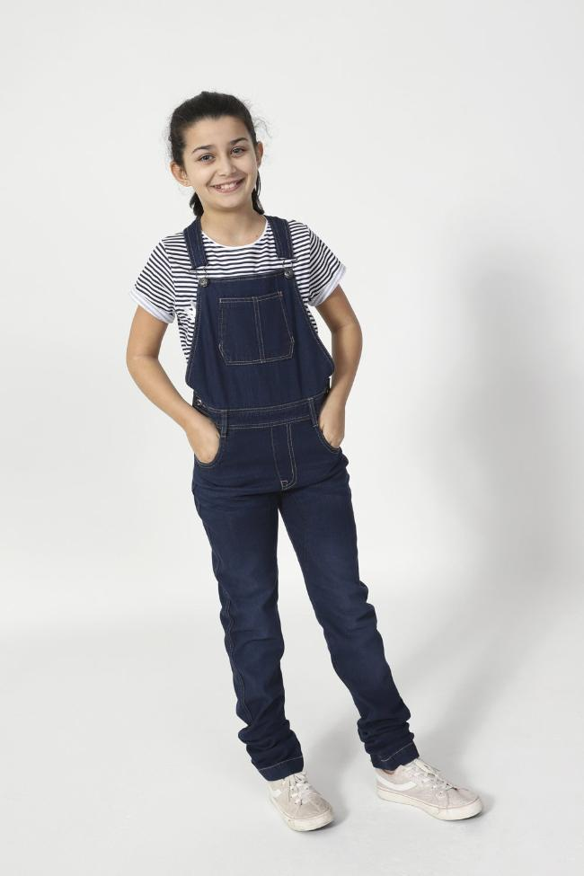 Full-frontal pose with hands in front pockets wearing Libby-style indigo dungarees with large bib pocket.