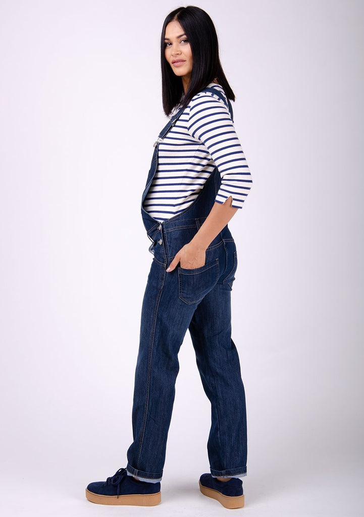 Full side pose to her right showing off bump wearing WASH Clothing Company's dark wash blue denim dungarees.
