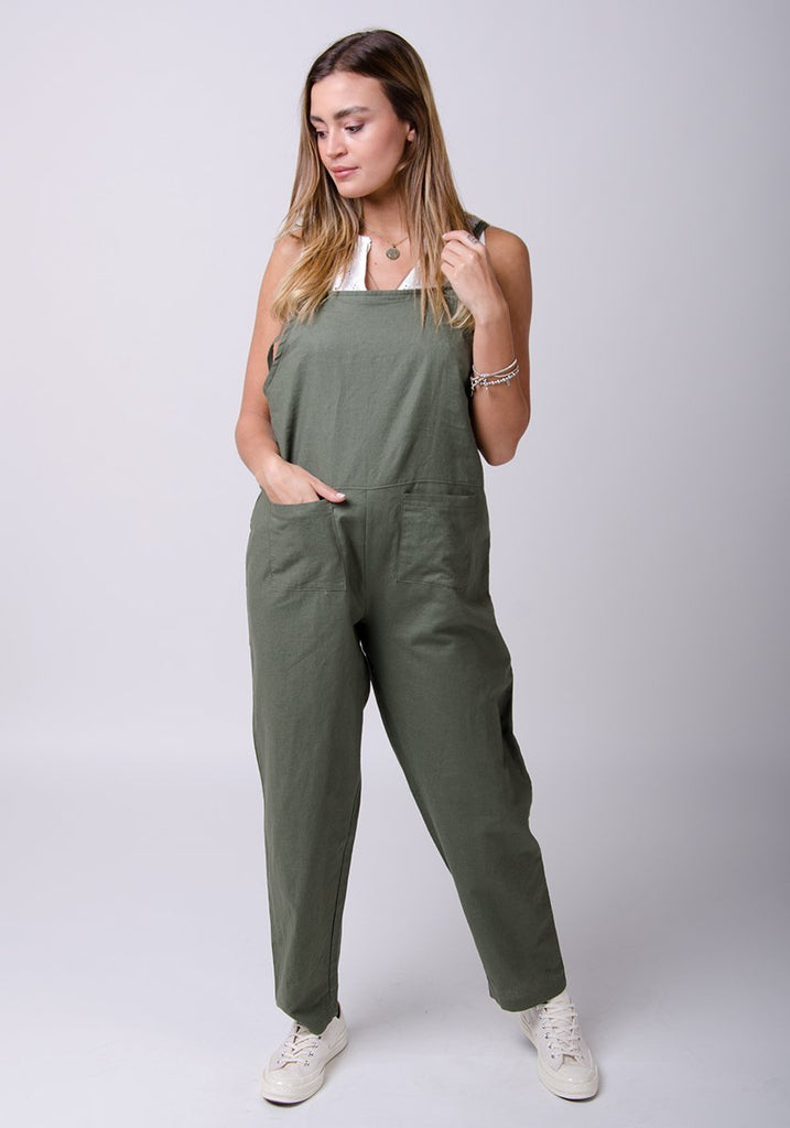 Full-frontal pose with right hand in pocket, looking to her right. Wearing practical, Roxanne-style linen dungarees.