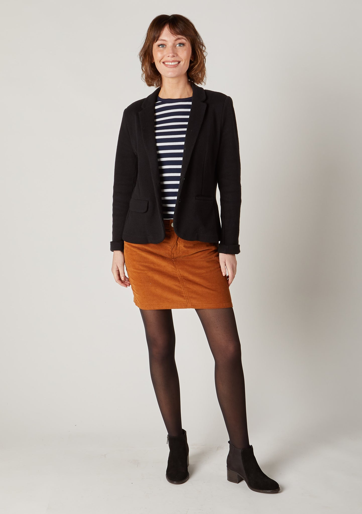 Full-length front pose of brown mini cord skirt styled with a smart black jacket.