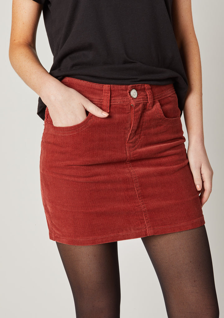 Close Shot focussing on zip and button fastening and hand in side pocket of Jacey short cord skirt