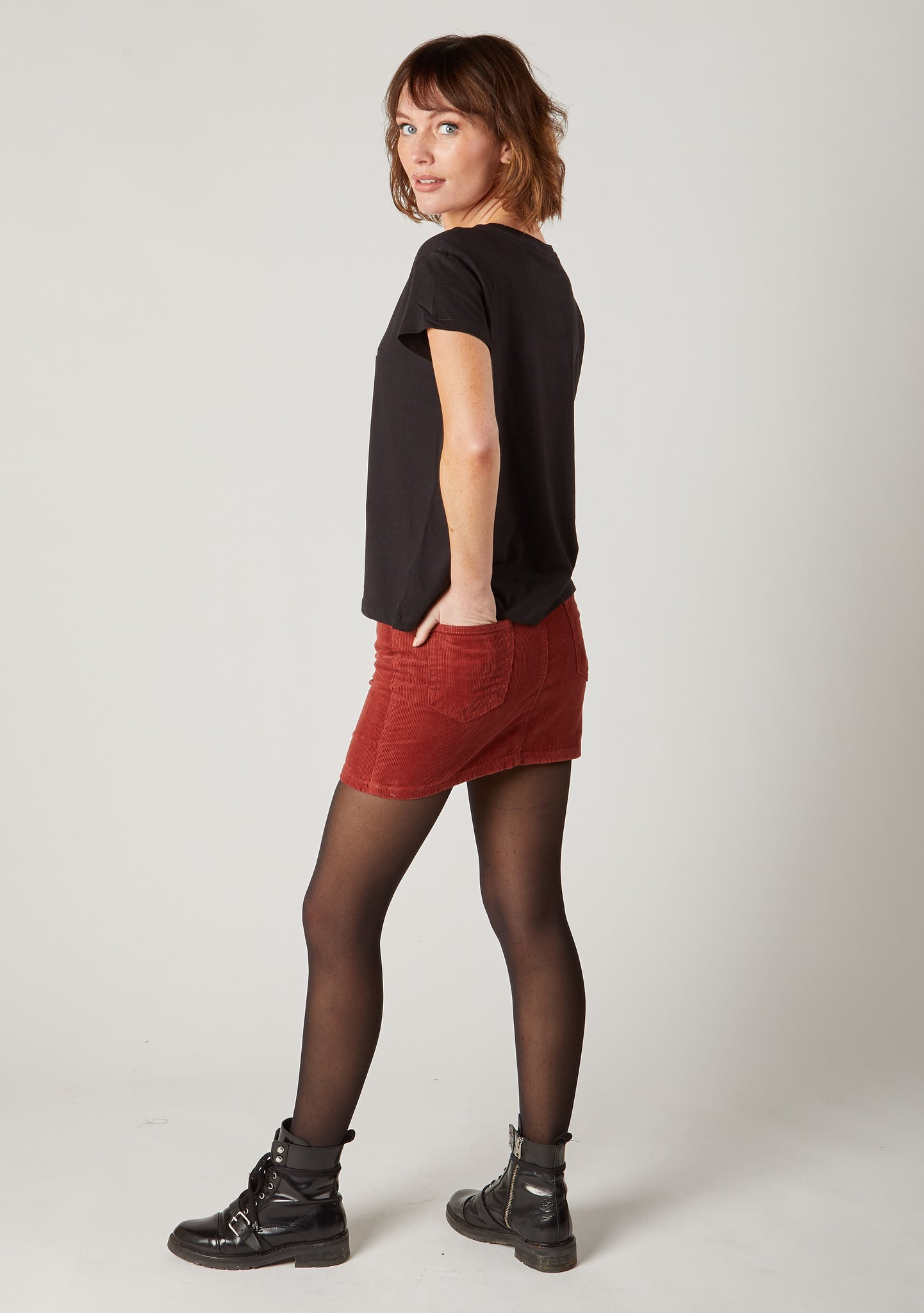 Two-thirds pose red corduroy mini skirt with hand in back pocket