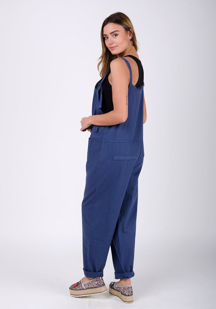 Full-side pose looking over her shoulder, wearing blue linen jumpsuit.