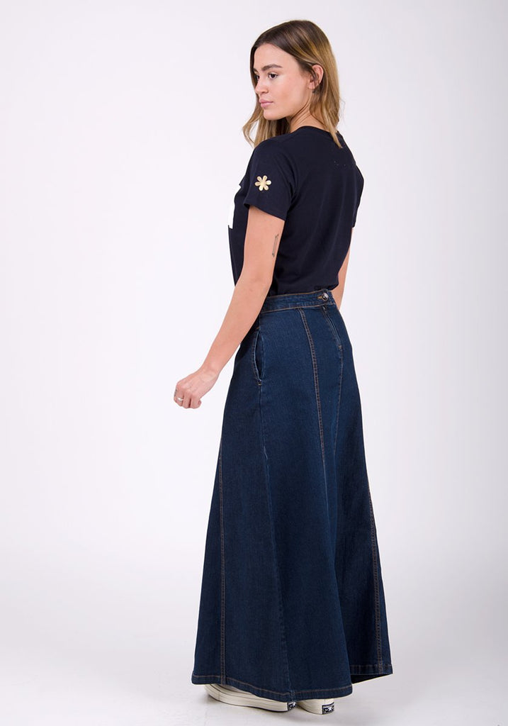 Full side pose looking to her left, focussing on dark wash denim texture.