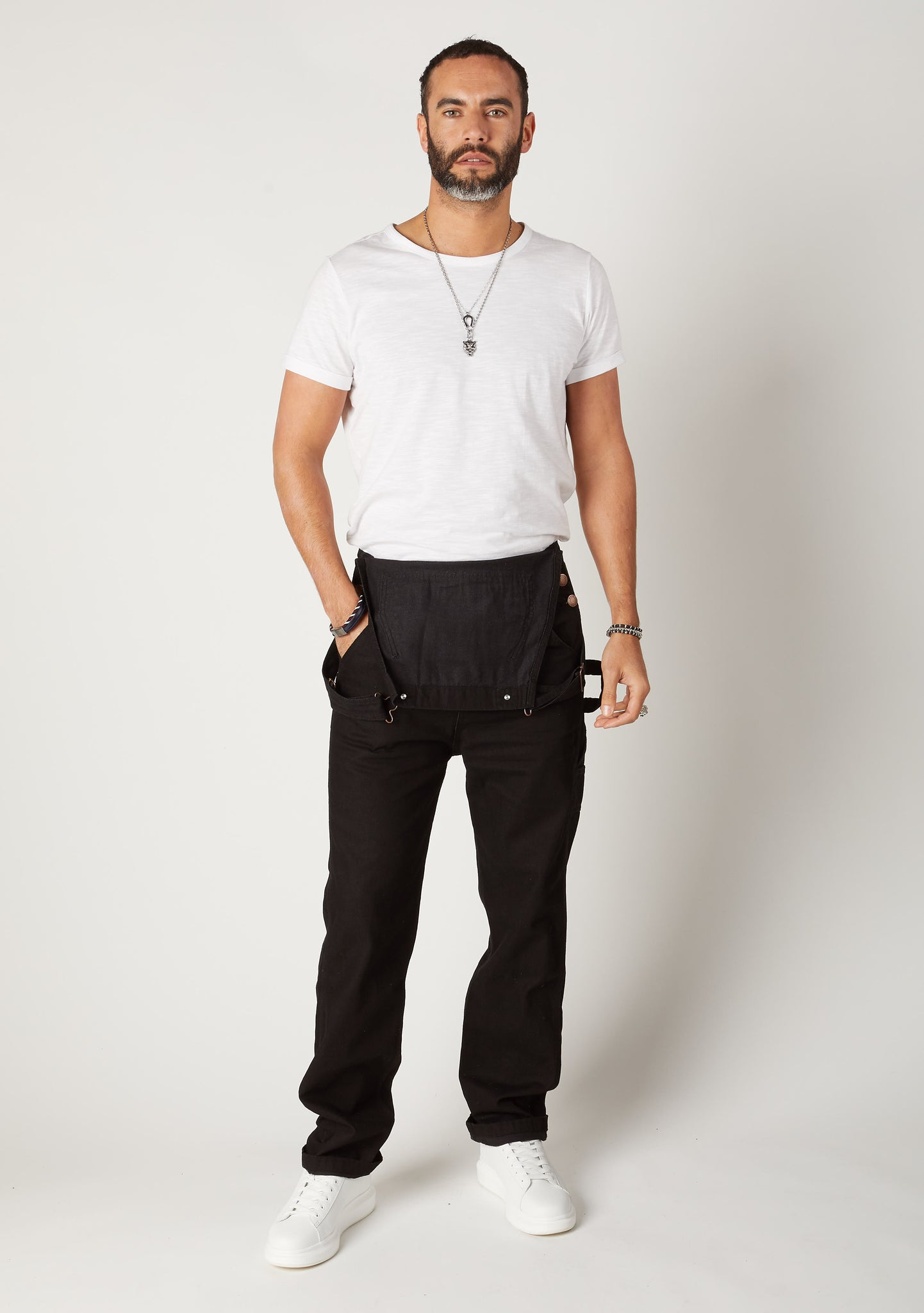 Front full-length pose of men's black denim overalls styled with bib down