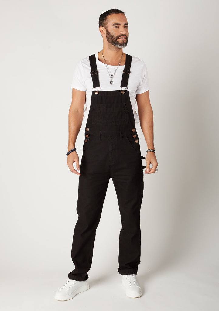 Full frontal pose looking to his left, wearing durable black overalls.