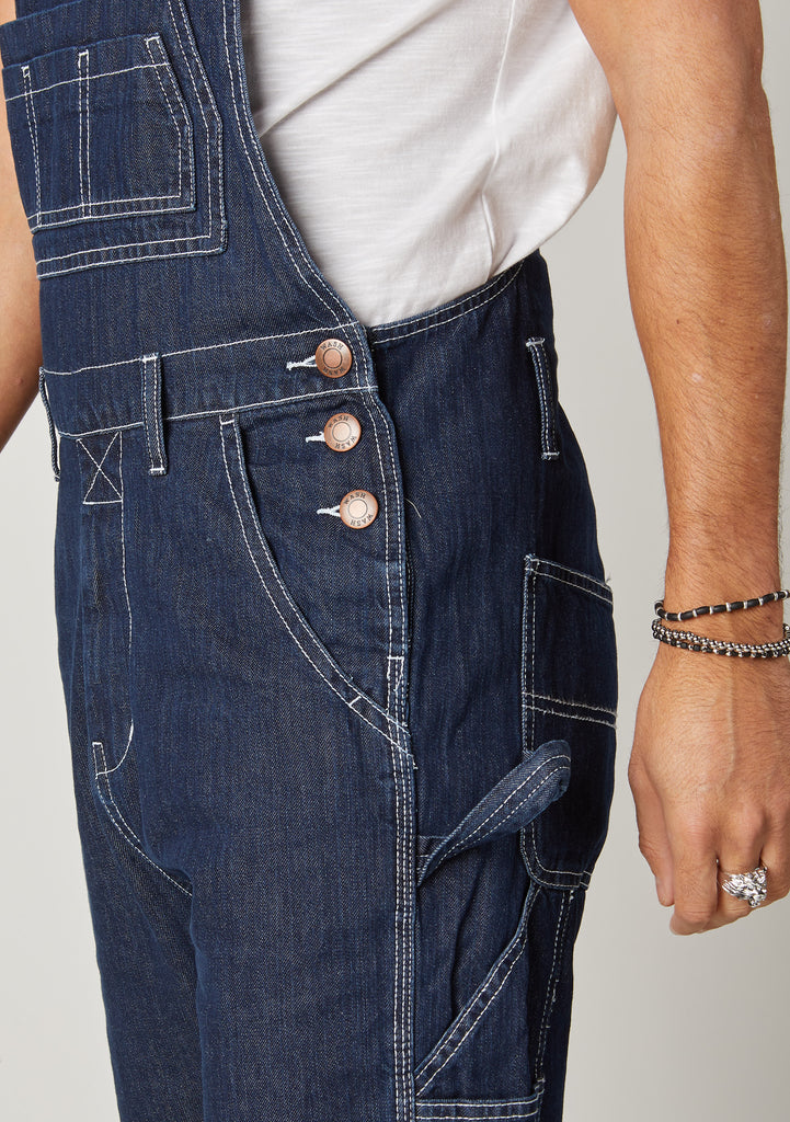 Close-up of Maddox Dark Blue Denim Dungarees for men showing the side three button fastening.
