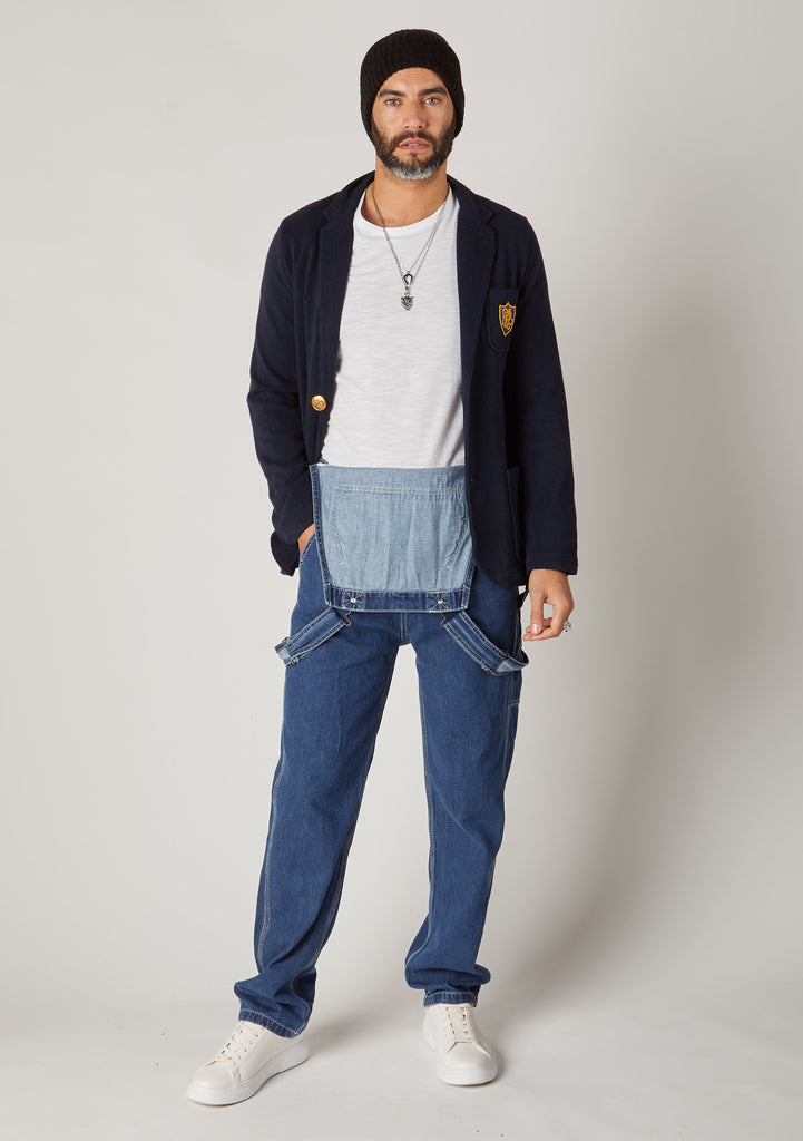 Front full-length pose of men's blue denim bib-overalls styled with bib down