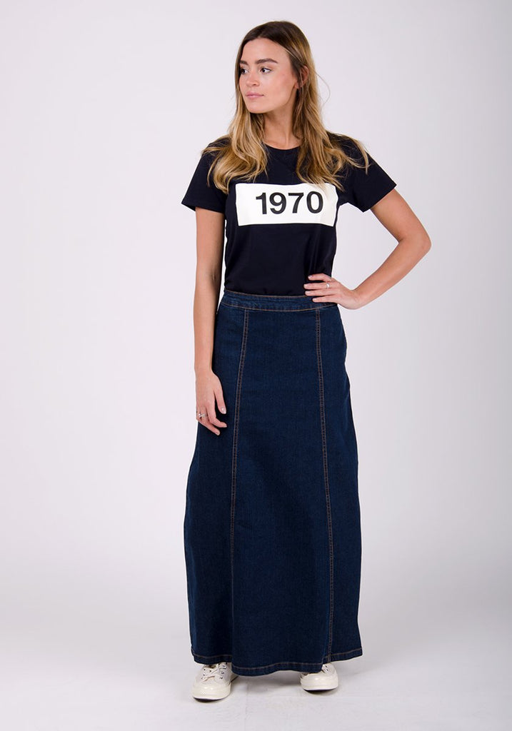 Full-frontal pose looking to her right with left hand on hip, wearing darkwash denim maxi skirt with side pockets.