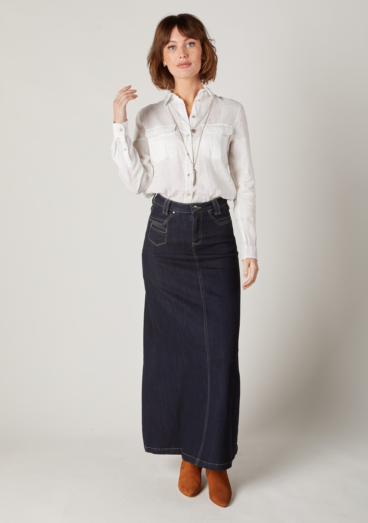 Full-length front pose of ladies modest ankle length dark wash jean skirt showing front zip fastening and pockets