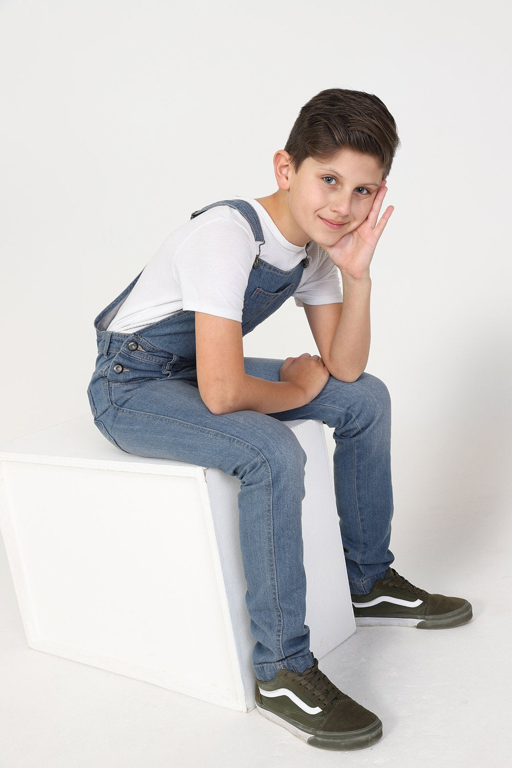 Side-view of boy sitting on box wearing durable zip fly, machine washable dungarees.