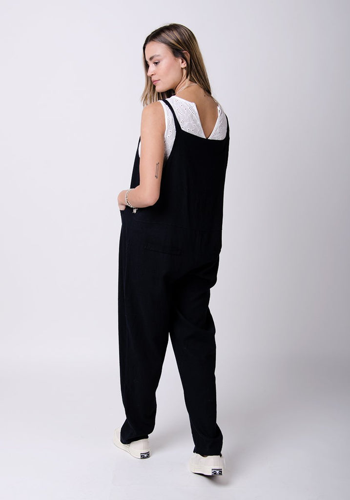 Full-rear pose looking to her left, showing adjustable straps and back pockets.