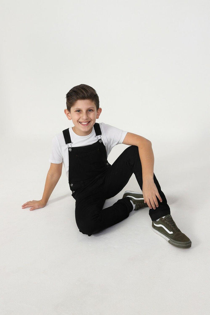 Boy sitting on floor wearing stylish kids bib-overalls.