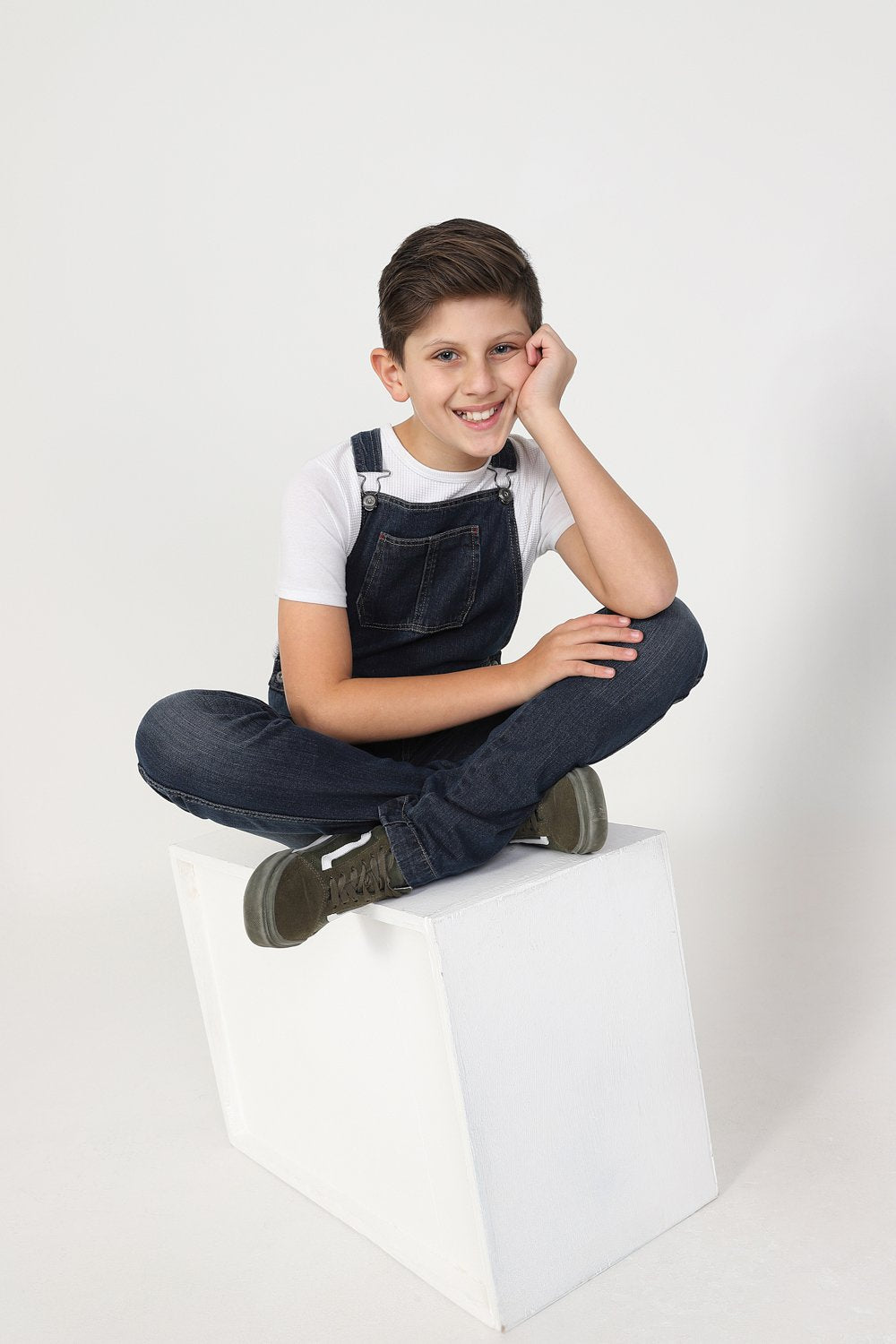 Smiling boy, cross-legged on box wearing modern, machine washable dungarees.