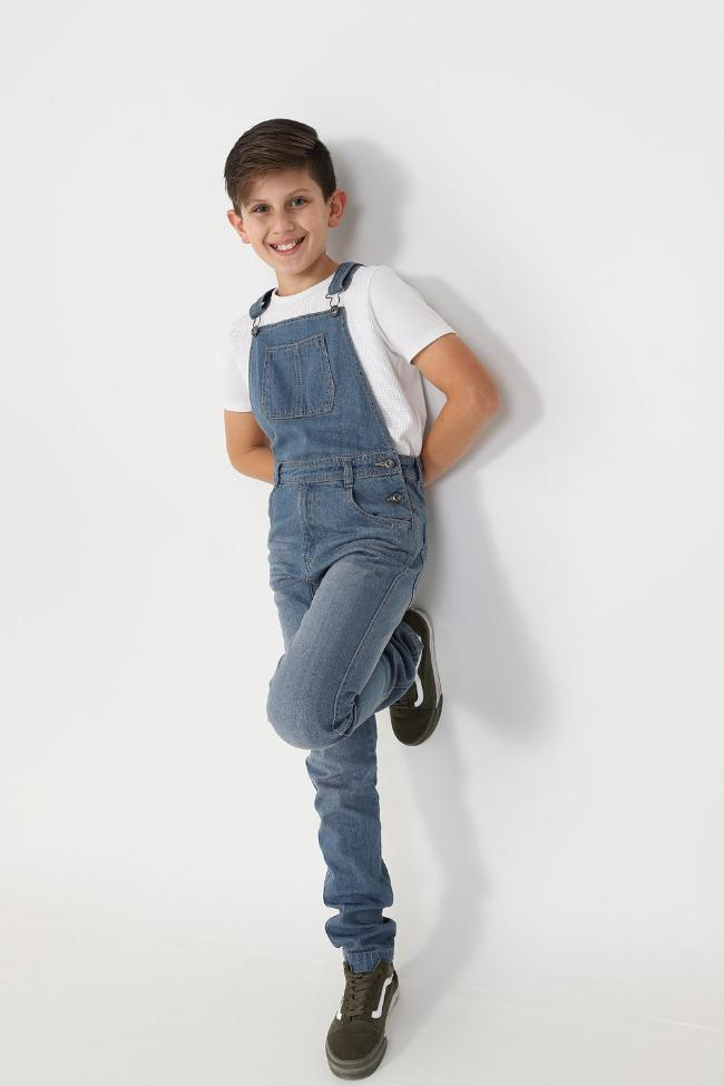 Full frontal leaning against wall with hands behind back, wearing boys light wash denim overalls.