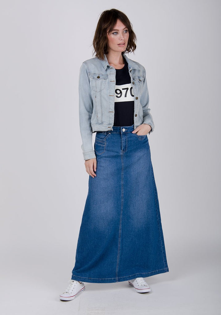 Frontal pose paired with light denim jacket, looking to her left, showing A-line silhouette of skirt,