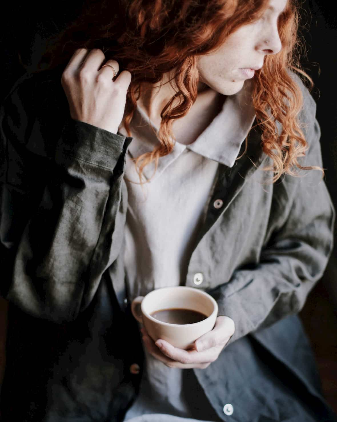 Woman holding coffee cup wearing linen coat