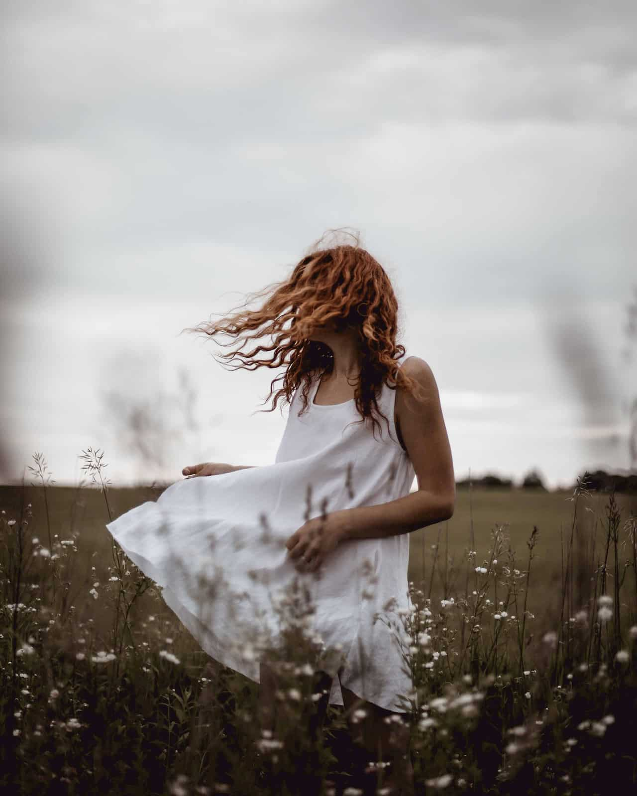 Woman wearing white linen dress in a field