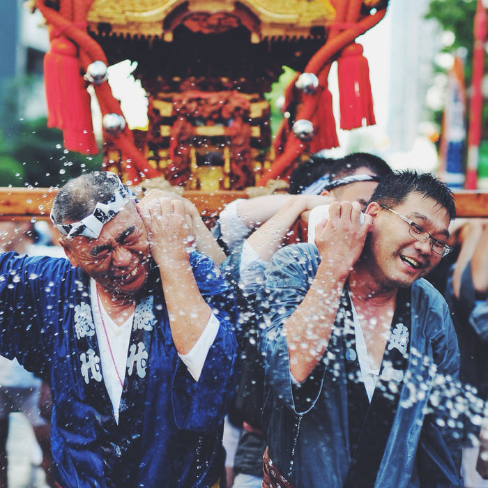 Japanese men carrying an omikoshi shrine at a matsuri festival