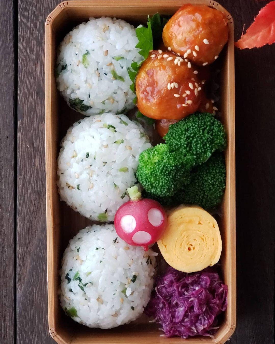Three round onigiri rice balls with colorful vegetables and meatballs