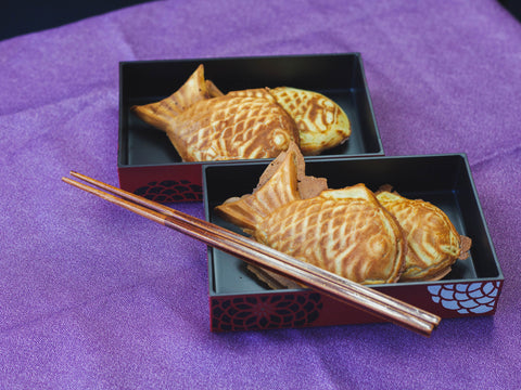 Taiyaki Japanese fish-shaped cakes in a bento box with chopsticks