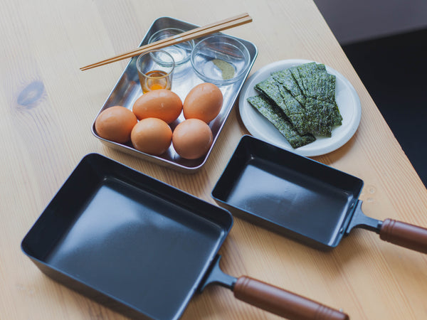 Two Tamagoyaki pans together with eggs and nori seaweed