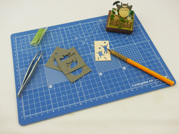 Cutting mat with tweezers, a craft knife and a paper diorama of the Ghibli movie My Neighbor Totoro