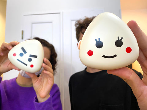 Two people holding up two plastic onigiri boxes covering their face.