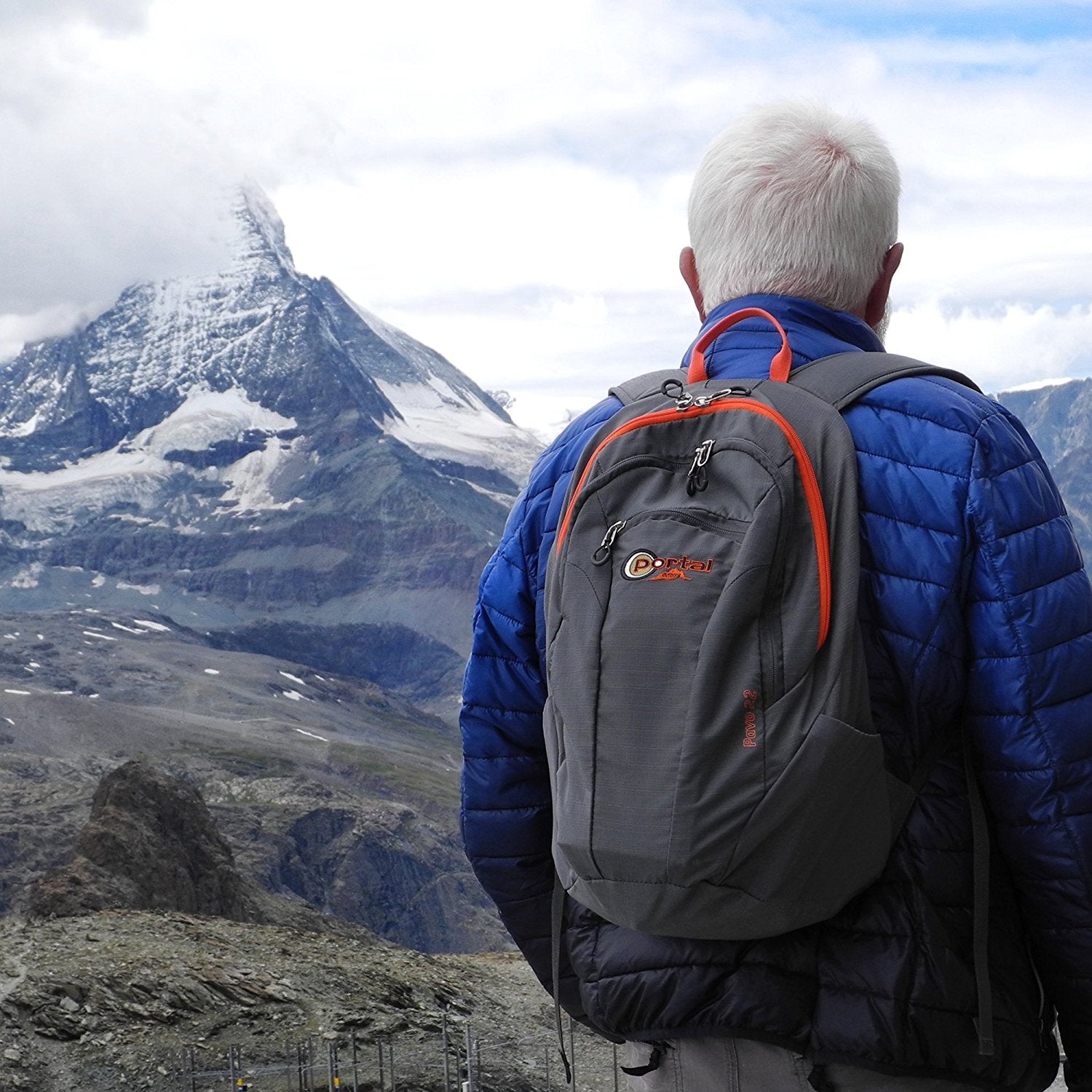 Image of man wearing Portal Outdoor Pavo 22 backback standing in front of a mountain.