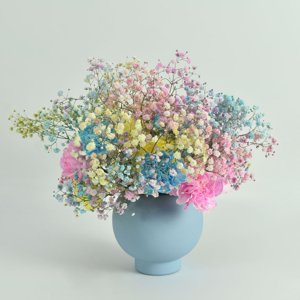 Arrangement includes multi colored baby's breath, blue, yellow, and pink dianthus designed in a baby blue vase.