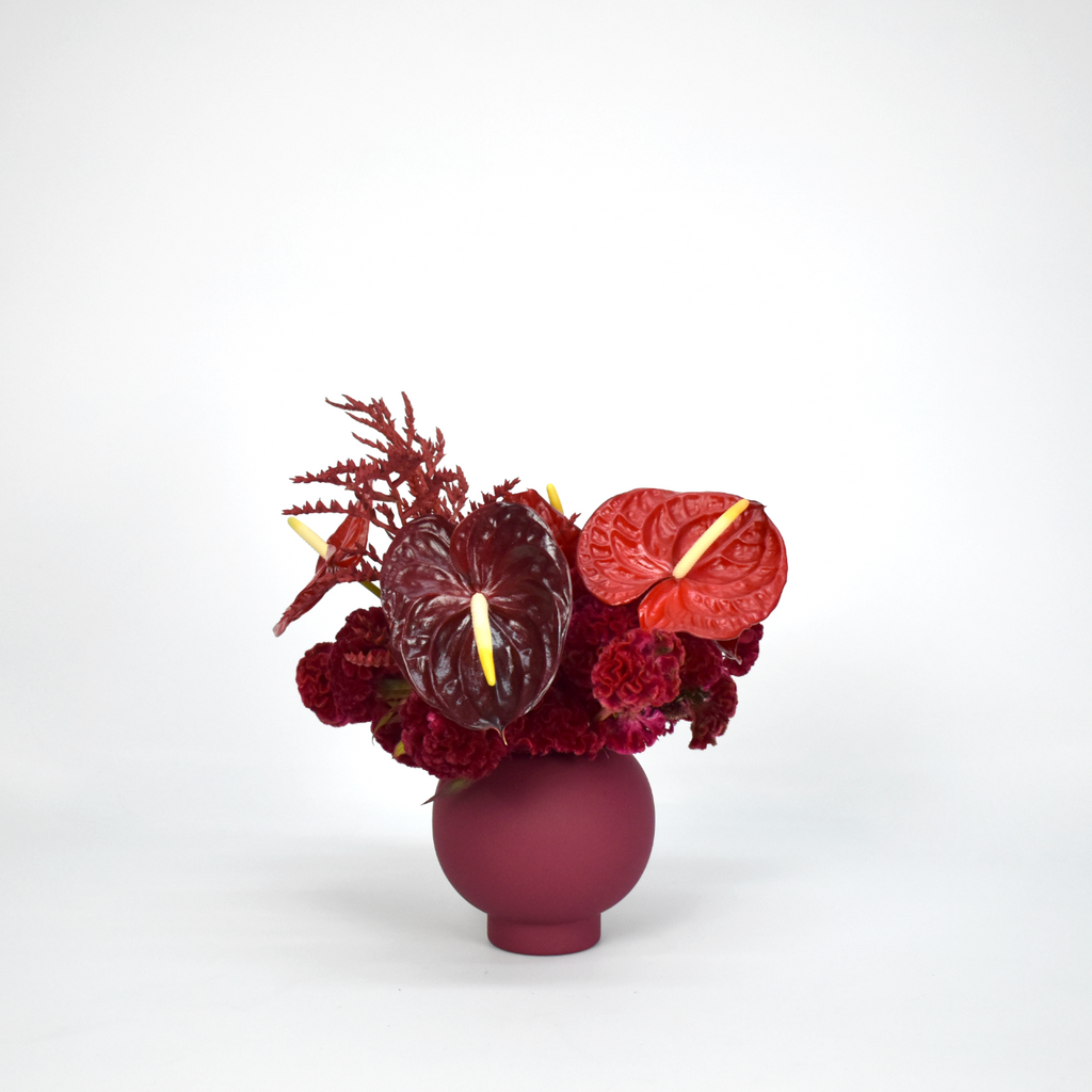 Arrangement includes two shades of red anthurium, red coxcomb, and red bromeliad designed in burgundy mushroom vase. It is non-fragrant arrangement..