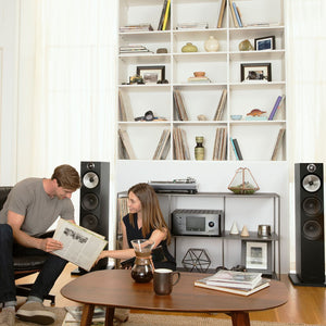 2 black 603 floorstanding speakers next to bookshelf with people listening to music
