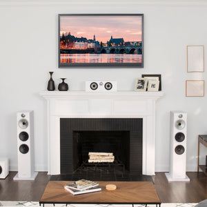 2 white 603 floorstanding speakers next to fireplace and painting