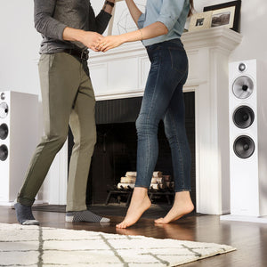 Couple dancing next to 2 white 603 floorstanding speakers