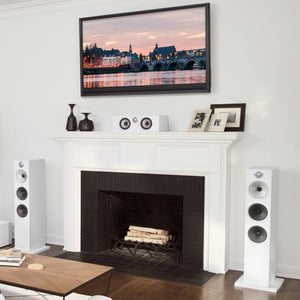 White HTM6 center channel speaker on fireplace next to 2 white floorstanding 603 speakers
