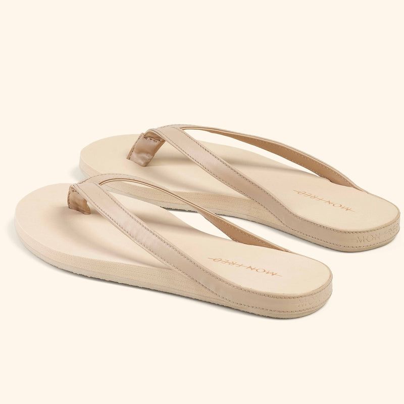 Angle view of a pair of beige Mon Fred flip flops