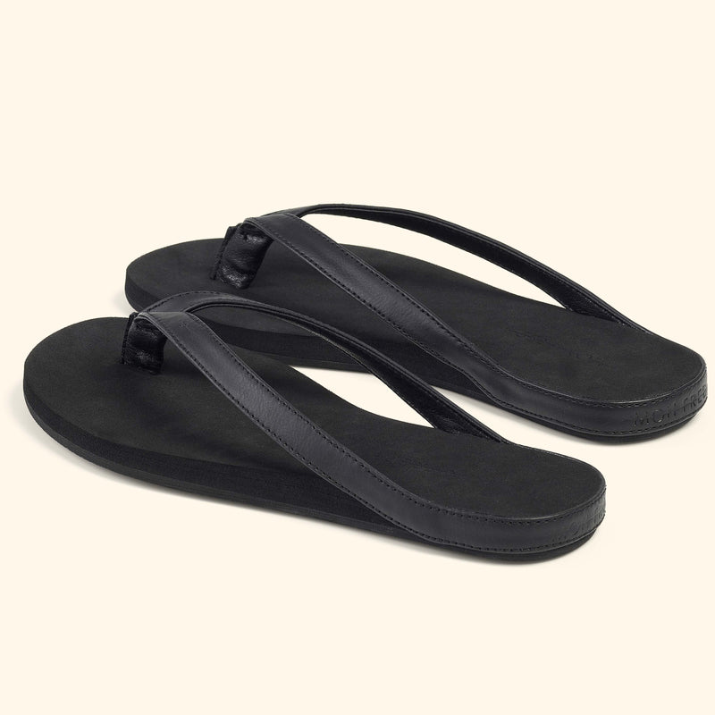 Angle view of a pair of black Mon Fred flip flops