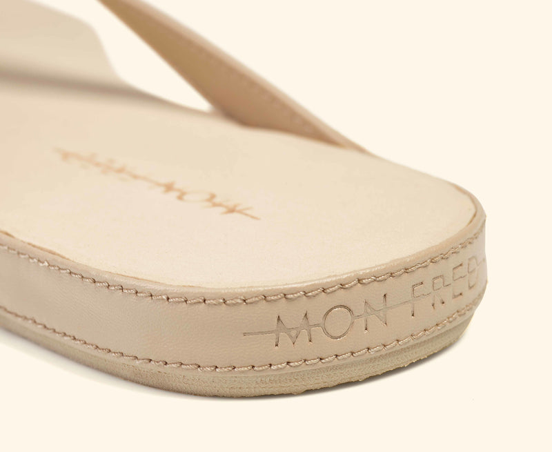 Detailed view of a beige Mon Fred flip flop strap