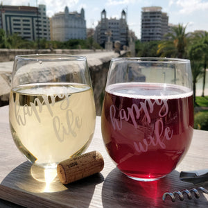 Funny Happy Wife and happy life quote stemless wine glass set of 2 with red wine and white wine on wood table top over looking city landscape with wine opener