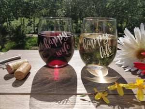 Funny Happy Wife and happy life quote stemless wine glass set of 2 with red wine and white wine on wood table top in city park with wine cork and flower bouquet