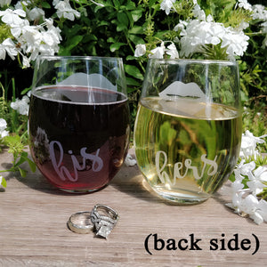 Stemless wine glasses with lips and mustache on front with his and her on back filled with red wine and white wine wood table top with wedding rings displaying his and her flower backdrop