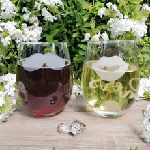 Stemless wine glasses with lips and mustache on front with his and her on back filled with red wine and white wine on wood table top and wedding rings in front of white flowers. | SMOOCHIES