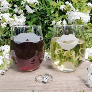 Stemless wine glasses with lips and mustache on front with his and her on back filled with red wine and white wine on wood table top and wedding rings in front of white flowers.