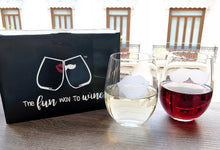 Stemless wine glasses with lips and mustache on front with his and her on back filled with red wine and white wine with SMOOCHIES box on wood table top over looking city through window