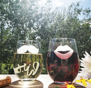 Stemless wine glasses with lips and mustache on front with his and her on back filled with red wine and white wine on wood table top with wine cork and flower boutique in city park with sun over looking tree line
