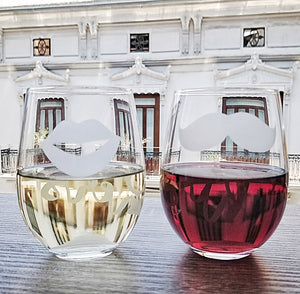 Stemless wine glasses with lips and mustache on front with his and her on back filled with red wine and white wine on wood table top in city over look